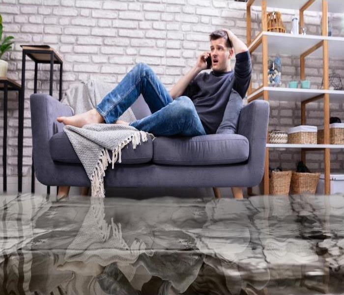 Flooded Floor Man Sitting On Sofa Calling for help